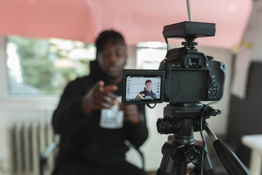 Hombre joven grabándose a sí mismo en una cámara de video