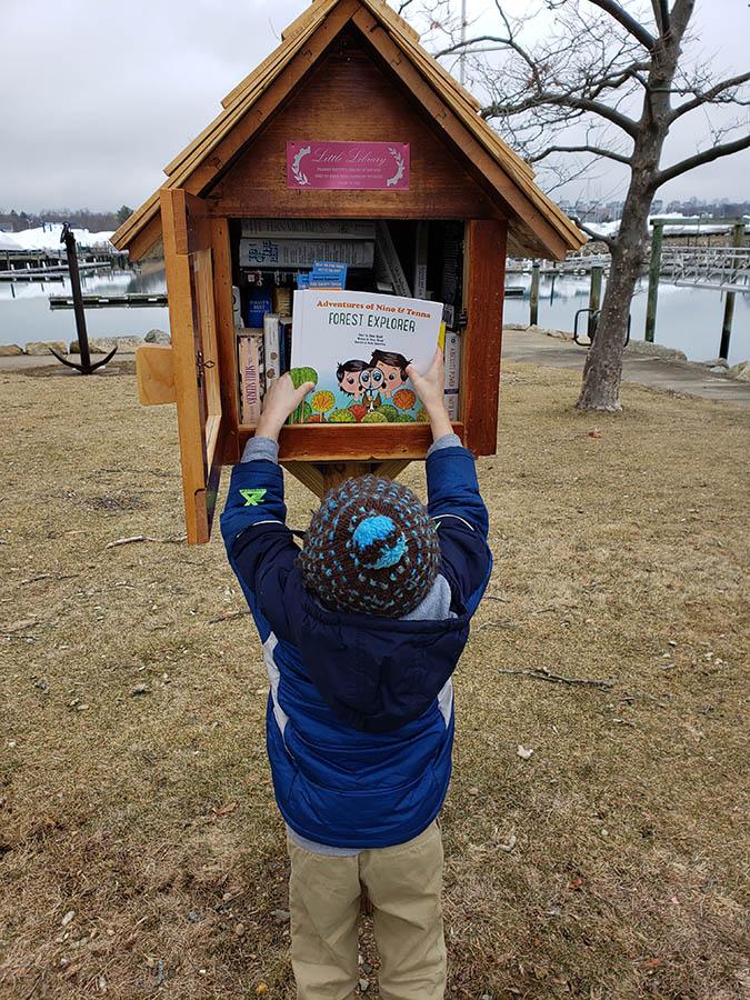 Ethan y su hijo dejando algunas copias de una historia en las cajas de Little Library en la ciudad
