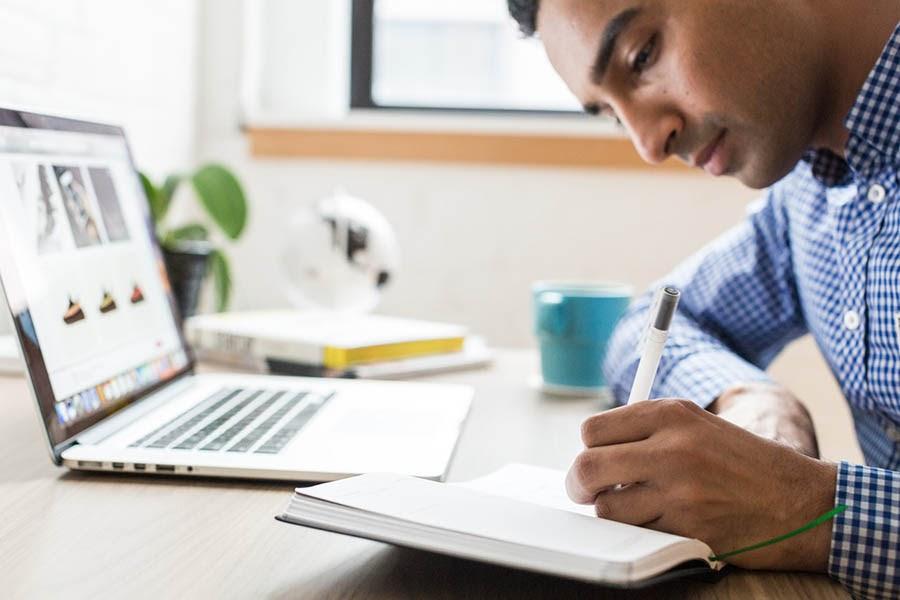 Un hombre sentado en un escritorio escribiendo en una libreta.