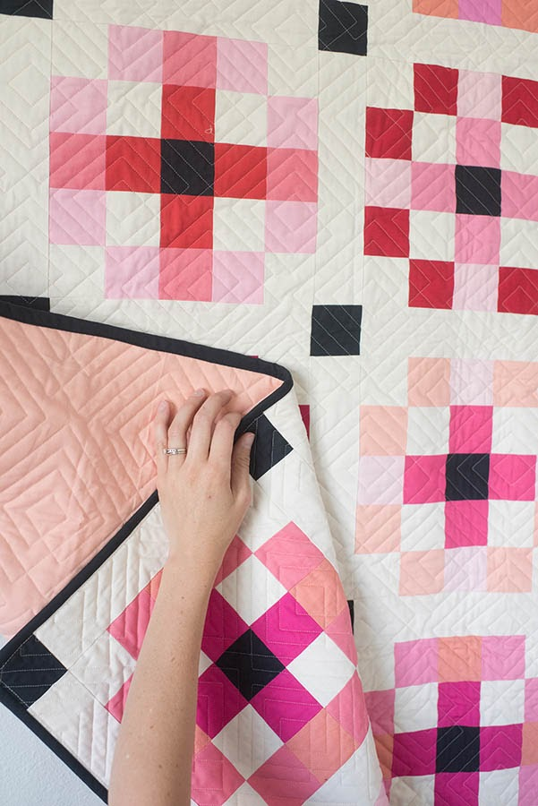 Hand touching quilt with flower pattern.