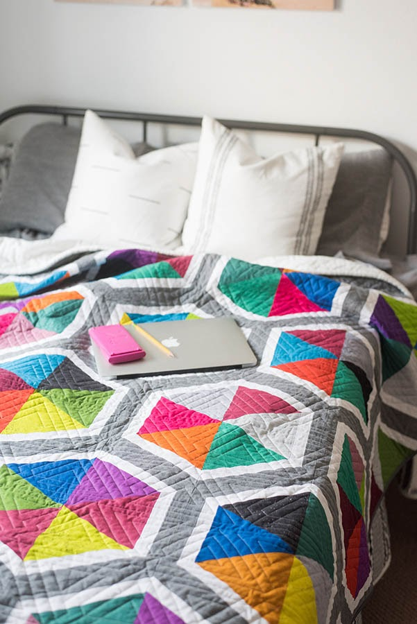 Bed with bright colorful quilt and laptop on top of bed.