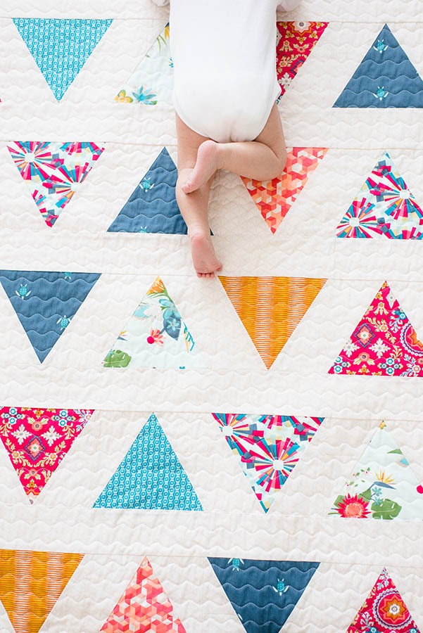 Baby crawling on quilt with flower triangle pattern.