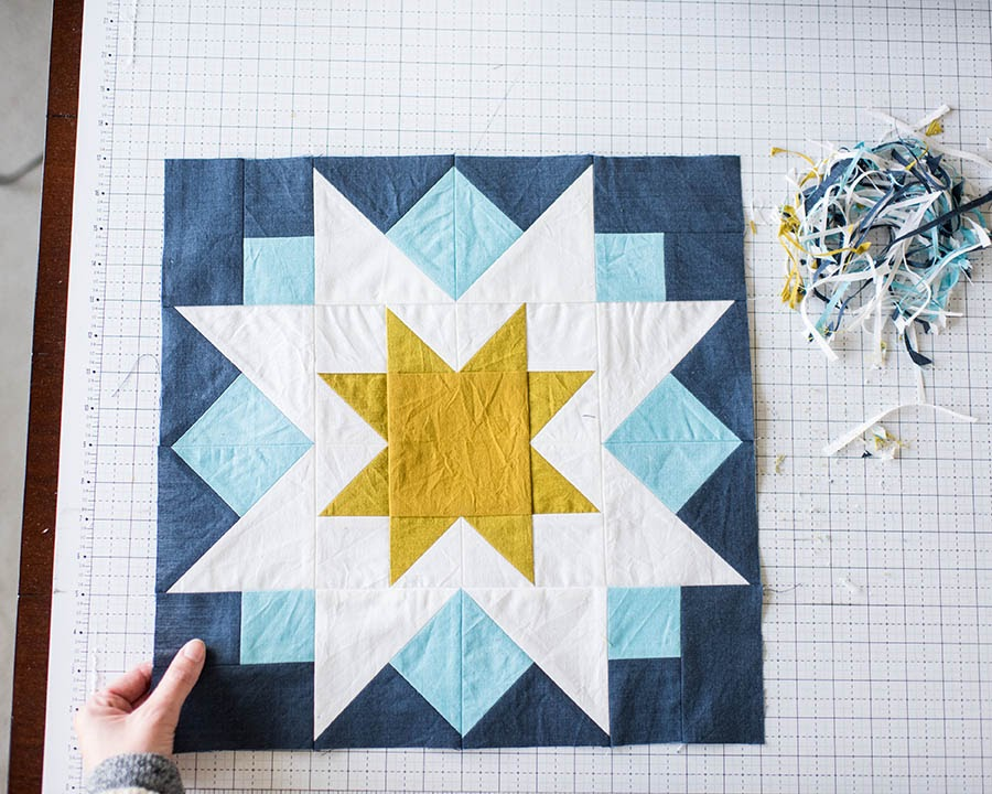 Hand touching quilt pattern with blue sun triangle pattern on cutting board.