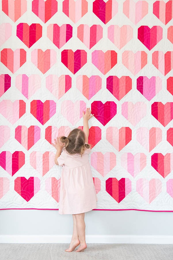 Toddler girl standing in front of heart pattern quilt hanging on wall.