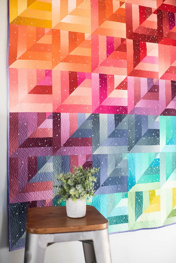 Quilt with bright modern geometric patterns and colors hanging on wall next to plant.