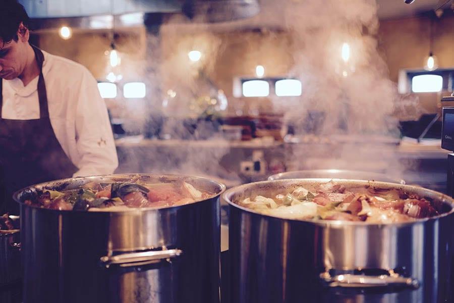 Chef en una cocina con ollas calientes